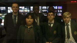 Students standing in front of the many screens in the newsroom
