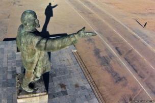 A woman walks past a statue of Soviet Union founder Vladimir Lenin