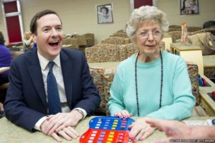 Britain's Chancellor George Osborne laughs during a visit to Castle Bingo in Cardiff