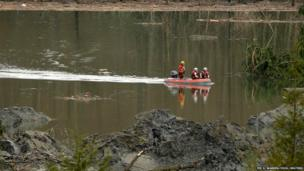 Rescuers use a boat as search work continues in the mud and debris from a massive mudslide that struck Oso near Darrington, Washington