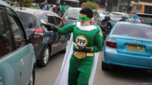 A supporter of United Development Party (PPP) wearing a superhero costume hands out brochures to drivers during a campaign rally on a street in Jakarta, Indonesia