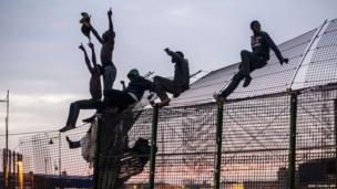 Would-be immigrants are seen on a fence near the Spanish enclave of Melilla