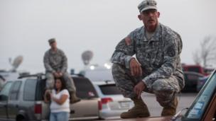 Staff Sgt John Robertson waits in a car park outside Fort Hood military base about the shooting there, 2 April 2014.