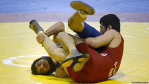 Turkey's Soner Demirtas (left) competes with Germany's Georg Harth in the Wrestling European Championships in Vantaa, Finland