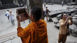 A Buddhist monk uses a tablet to take pictures as he visits the Angkor Wat temple in north-western Cambodia