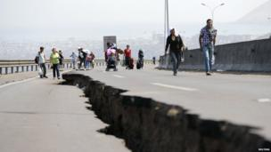 People walk next to a crack along a damaged road leading to Alto Hospicio commune in Iquique - 3 April 2014