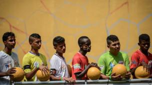 The captains from Pakistan, Brazil, Egypt, Burundi, Nicaragua and Mauritius (from L to R) wait in a line during the second edition of the Street Child World Cup in Rio de Janeiro, Brazil, on 1 April 2014