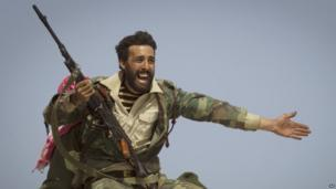 A Libyan rebel fighter urges people to leave as Col Muammar Gaddafi's forces start shelling the frontline near the town of Bin Jawaad. Photo: 2011