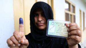 An Afghan woman shows her inked finger after casting a vote at a polling station in Jalalabad