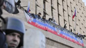 "Pro-Russian protesters stand behind a banner saying ""Donetsk Republic"" as they storm the regional government building in Donetsk on 6 April 2014."
