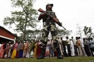 A security personnel stands guard as people line up to cast their vote outside a polling station in Tinsukia in Assam.