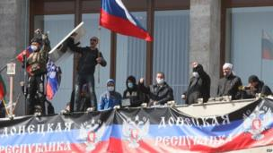 "Pro-Russian protesters who seized the main administration building in the eastern Ukrainian city of Donetsk wave a flag of their ""people's republic"", the Donetsk Republic, and hold a Russian flag."