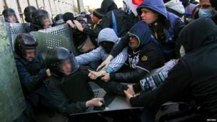 Pro-Russia protesters (R) scuffle with the police near the regional government building in Donetsk