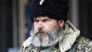 A pro-Russian armed man looks on near the mayor's office in Slaviansk on 14 April 2014