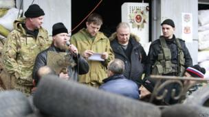 A clergyman (2nd L) addresses pro-Russian protesters during a rally, with a barricade seen in the foreground, in front of the seized office of the SBU state security service in Luhansk, eastern Ukraine on 14 April 2014