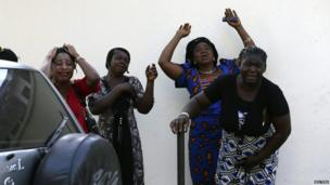 Bystanders react as victims of a bomb blast arrive at the Asokoro General Hospital in Abuja on 14 April 2014.