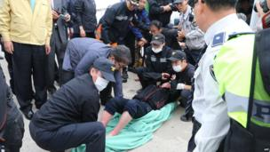 Rescue teams help one of the 476 passengers and crew who was on board a South Korean ferry as it capsized on 16 April 2014