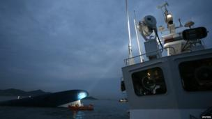 One of the boats involved in the search operation shines its spotlight on to the last part of the ferry left above the water - 16 April 2014