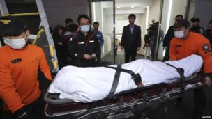 "A body of a passenger who was on South Korea ferry ""Sewol"" which sank in the sea off Jindo, is wheeled into an ambulance at a hospital in Mokpo on 17 April, 2014"