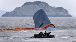A vessel involved in salvage operations passes near the upturned South Korean ferry on 17 April 2014.