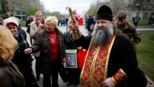 Ukrainian Orthodox priest sprinkles holy water on believers outside a government building in Donetsk, Ukraine, on 20 April 2014