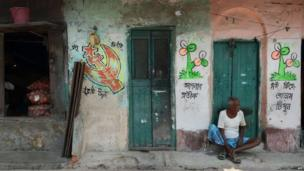 An Indian labour sits alongside graffiti in support of different political parties in Kolkata
