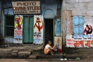 An elderly Indian woman washes clothes on her doorstep beside election graffiti of the Communist Party of India (Marxist) in Kolkata