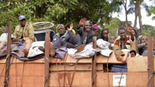Muslims who fled Bangui wave aboard a truck as they are escorted by French troops of the Sangaris Operation (not seen) in Grimari in the Central African Republic