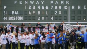 Survivors of the 2013 Boston Marathon bombings (L) and runners in this year's race (R) are honoured on the field during a pre-game ceremony before the American League MLB baseball game between the Baltimore Orioles and the Boston Red Sox at Fenway Park in Boston, Massachusetts
