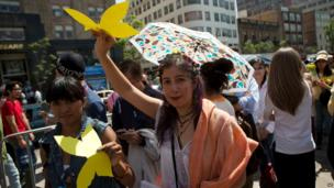 Well-wishers carry yellow butterflies outside the Palace of Fine Arts in Mexico City, April 21, 2014.