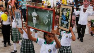 Residents hold portraits during a symbolic funeral in Aracataca, Colombia, April 21, 2014.