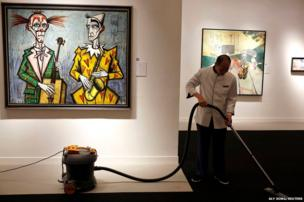 An employee vacuums the carpet next to Bernard Buffet's Deux clowns, saxophone during a media preview of Christie's Shanghai Spring Auction