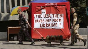 A pro-Russian separatist pulls a cart outside the seized office of the SBU state security service in Luhansk (24 April 2014)