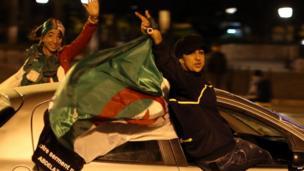 Algerians hanging out of a car waving a national flag, Algiers, Algeria - Friday 18 April 2014