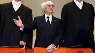 Formula One chief executive Bernie Ecclestone (centre) stands with his lawyers