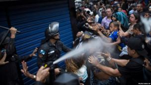 A woman is pepper sprayed as residents of Pavao-Pavaozinho slum clash with riot police