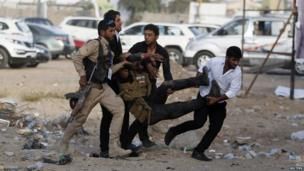 Men evacuate an injured person after a car bomb attack at a Shia political organisation's rally in Baghdad on 25 April 2014.