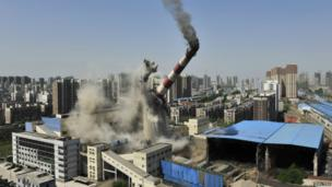 A 150m-high chimney, the tallest in the Chinese city of Shenyang, is demolished so that it can be replaced with a more eco-friendly one - 28 April 2014.