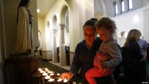 A woman and child light a candle in Corpus Christi Catholic Church after teacher Ann Maguire was fatally stabbed at Corpus Christi Catholic College in Leeds