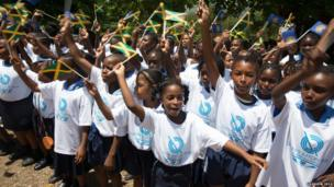 A group of young children all waving small Jamaican national flags.