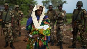 The relative of a woman who recently gave birth to twins holds one of the babies before departing Bangui for Chad, under escort by soldiers of the African Union operation in Central African Republic