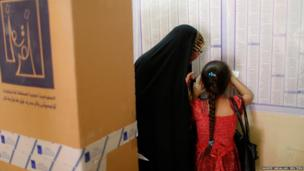 A girl helps her grandmother as she searches for her name before voting at a polling station, during a parliamentary election in Baghdad