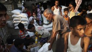 Rohingya people receive their share of food aid from the World Food Program (WFP) at the Thae Chaung camp for internally displaced people in Sittwe, Rakhine state (April 2014)