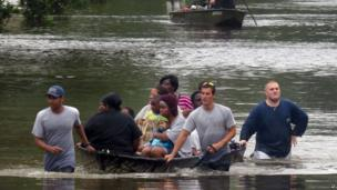 Residents at the Forest Creek Apartments in Pensacola, Florida are rescued by boat 30 April 2014