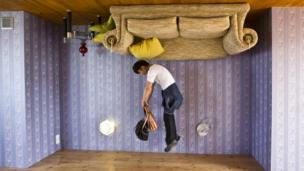 Man jumps inside upside-down house.