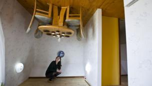Woman poses in upside-down house.