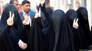 Women gesture with their ink-stained fingers after casting their vote in Baghdad, Iraq