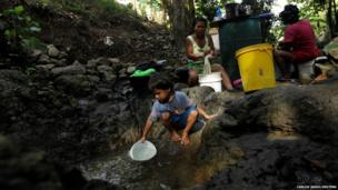 A boy collects water from a rock pool as women wash clothes on the outskirts of Panama City