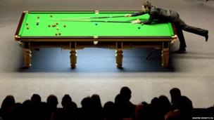 Snooker player Ronnie O'Sullivan plays a shot