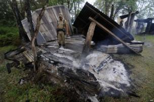 An Indian security official examines the remains of a still smouldering dwelling in the village of Khagrabari in Assam.